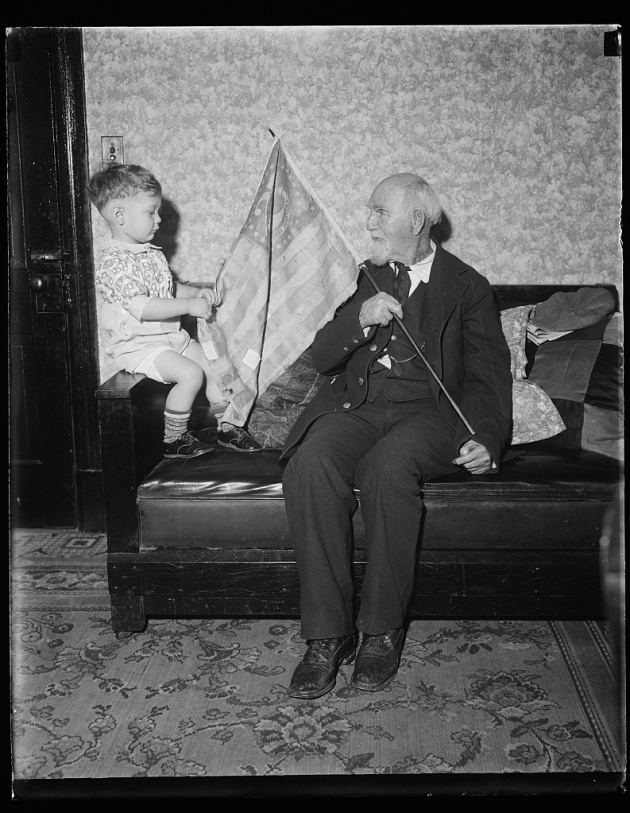 Union Veteran Orlando Learned shows a flag he obtained at Vicksburg to his Great-Grandson, 1931 (Library of Congress)