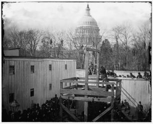 A soldier springs the trapdoor, with men looking on from the trees beyond (Library of Congress)