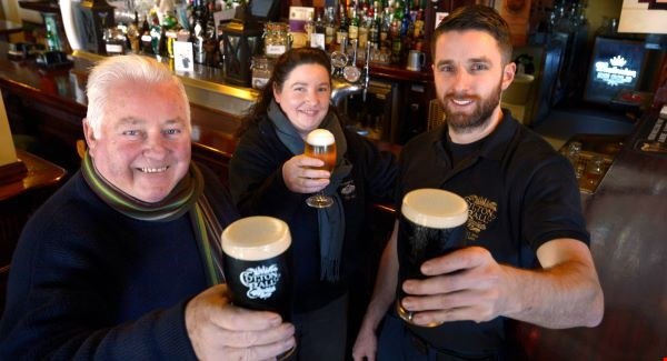 Jack Lynch (left) and his family in the bar established by his grandfather Humprhey, a veteran of the 4th U.S. Artillery in the Civil War (Irish Examiner)
